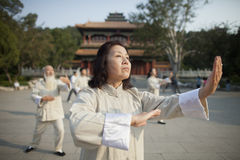 Kinesiskt folk som framme öva Tai Ji av byggnad för traditionell kines arkivbilder