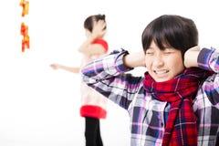 kinesiskt lyckligt nytt år barn som spelar med firecrackeren Royaltyfri Bild