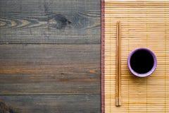 Kinesiskt målbegrepp soya i bunke nära pinnar och bambuunderlägget på mörkt träutrymme för bästa sikt för bakgrund royaltyfri fotografi