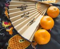 Kinesiskt nytt år, tangerin och en fan som ligger på det siden- tyget med en broderad drake Royaltyfri Foto