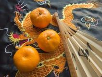 Kinesiskt nytt år, tangerin och en fan som ligger på det siden- tyget med en broderad drake Royaltyfri Bild