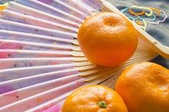 Kinesiskt nytt år, tangerin och en fan som ligger på det siden- tyget med en broderad drake Royaltyfri Fotografi