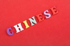 KINESISKT ord på röd bakgrund som komponeras från träbokstäver för färgrikt abc-alfabetkvarter, kopieringsutrymme för annonstext Royaltyfri Fotografi