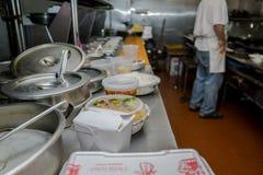 Kinesiskt ta ut beställningar på tabellen med bakgrundskocken Arkivbilder