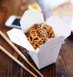 Kinesiskt ta ut med den smarta telefonen på tabellen och meny Arkivbild