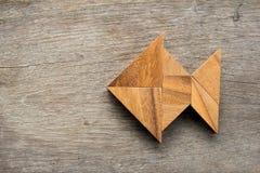 Kinesiskt tangrampussel i fiskform på wood bakgrund royaltyfri fotografi