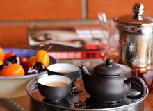 Kinesiskt te, frukter, tillbringare och bok på tabellen Arkivbild