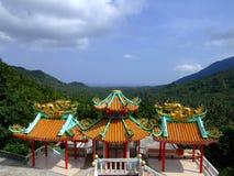Kinesiskt tempel ovanför djungelliggande. arkivfoton