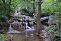 Kinesiskt vatten med stenar Arkivfoto