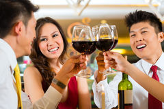 Kinespar som rostar med vin i restaurang Arkivfoton