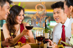 Kinespar som rostar med vin i restaurang Arkivbild