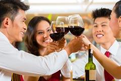 Kinespar som rostar med vin i restaurang Arkivbilder