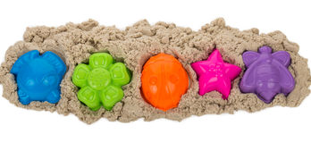 Kinetic sand with multicolored molds. Isolated on white Royalty Free Stock Image