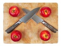 2 kinfes пересеченного на прерывая доску с яблоками Стоковое Фото