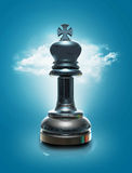 The King. A 3D glossy black chess king standing on a reflective ground with a sky full of clouds in the background Stock Photo
