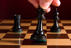 King being moved by hand on chess board. Chess board with king as example of game or business concept for power; strategy or success royalty free stock photography
