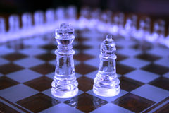 King and Bishop chess pieces. Closeup of ice blue glass King and Bishop chess pieces on board Stock Images