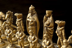 King on Black. Closeup of a chess board with pieces, focus is on the King with the Queen and one of the Bishops in the DOF as well. The board with both sides stock image