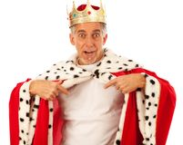 King With Blank T-shirt. Senior man wearing a king`s robe and crown, pointing at his white t-shirt Stock Photo