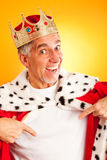 King With Blank T-shirt. Senior man wearing a king`s robe and crown, pointing at his white t-shirt Stock Image