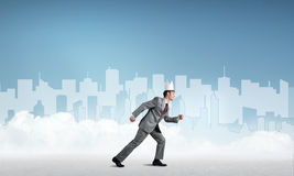 King businessman in elegant suit running and blue cityscape silhouette at background Stock Images