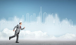 King businessman in elegant suit running and blue cityscape silhouette at background Stock Photos