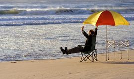 King Canute lives. Businessman sat on a chair in business attire under a colored umbrella with the waves rolling towards him Stock Photos