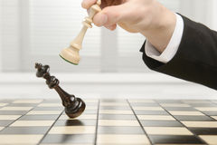 King Checkmate. High key image of a Chess board. Checkmate by the black Pawn royalty free stock images