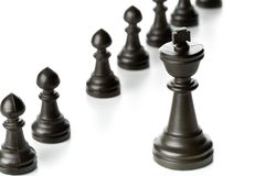 King chess figure in front of row of pawn chess figures royalty free stock photo
