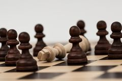 King in chess has fallen to several pawns Stock Photos