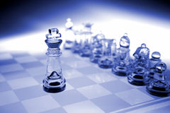 King chess piece and team. Glass King chess piece arranged in front of the other chess pieces as if leading or directing them...business metaphor for leadership stock image
