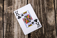 King of Clubs Card on Wood. King of Clubs from a deck of cards laying on vintage wood table background - old west salon style Stock Images