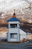 King Cove Alaska Russian Ortadox Church. With snow covered mountain in the background royalty free stock image