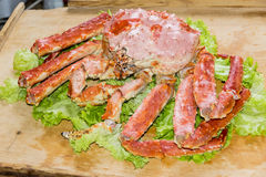 King Crab. Large king crab on lettuce leaf on a wooden background stock photography