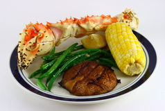 King Crab Leg, Corn, Potato. A dinner plate with a king crab leg, a cob of corn, green beans and a potato stock images