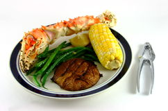 King Crab Leg with Cracker. A king crab leg, a cob of corn, green beans and a potato. A crab cracker sits next to the dinner plate royalty free stock photo