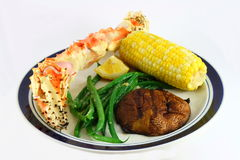 King Crab Leg Dinner with Corn. A dinner plate with a king crab leg, a cob of corn, green beans and a potato stock image
