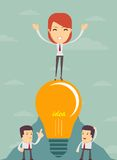 King of the hill. Young successful businesswoman proudly standing on the top. Happy woman celebrating his success With the idea in light bulb Royalty Free Stock Photography