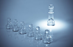 King and His Pawns. King in spotlight in front of his pawns Royalty Free Stock Images