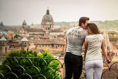 The king, his queen. Romantic couple in Rome, Italy. Two young people, a men and a women are kissing and loving. On a terrace with railing overlooking Rome, the stock photography