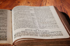 King James Bible Book of Psalms on Rustic Wooden Background. Closeup of an old Holy Bible opened to the famous Book of Psalm on a rustic wooden table. Deliberate Royalty Free Stock Image