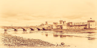 King Johns Castle in sepia. Stylized sepia image of a King Johns Castle and an old bridge over river Shannon, Limerick, Ireland Stock Images
