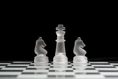 King & Knights. King and two knights on the chess board with black background good for copy space Royalty Free Stock Images