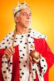 The King Lives. Senior man wearing a king`s attire, looking serious stock photo