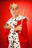 The King Lives. Senior man wearing a king`s attire, looking serious stock photography