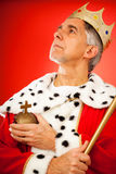 The King Lives. Senior man wearing a king`s attire, looking serious stock image