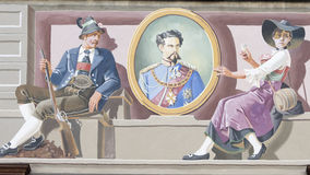 King Louis II Fresco on House, Bavaria. Bavarian house with painted couple holding picture King Louis II of Bavaria Royalty Free Stock Images