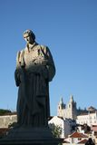 King Manuel I statue, Lisbon. On the foreground, the statue of King Manuel I, and on the background one church of Alfama area, in Lisbon, the most traditional royalty free stock images