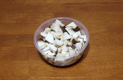 King oyster Mushroom or Pleurotus Eryngii cut into pieces in the. Clear plastic cup on the wooden table Stock Image