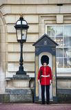 Queen palace guard london. King Palace guard in red uniform and bearskin hat standing at their post stock photos